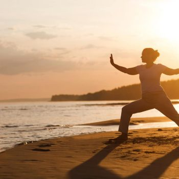 A woman practices Qi Gong during a wellness retreat amid the shore of Cape Breton Island.